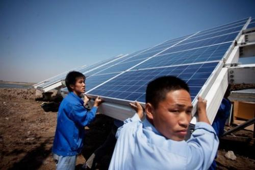 Workers install solar panels at the Sino-Singapore Eco-city near Tianjin on June 11, 2012
