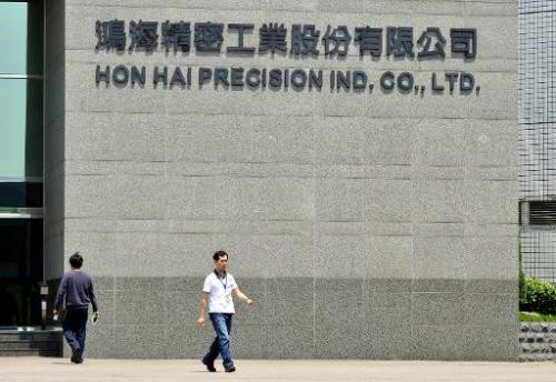 Workers walk in front of Hon Hai's headquarters in Tuchung city, northern Taiwan on June 7, 2010