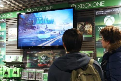 Youth look at a screen presenting a game for the new XBox One game console on November 22, 2013 in Paris