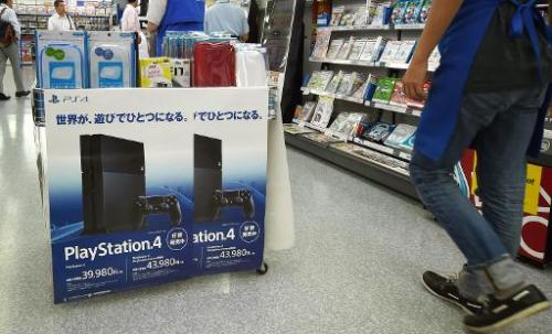 A customer walks past an electronics store display for Sony's PlayStation 4 video game console in Tokyo on August 13, 2014