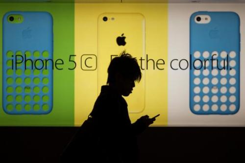 A man uses his phone as he walks past an Apple store in Hong Kong on December 25, 2013