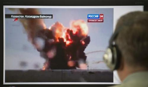 A man watches a computer screen in Moscow showing footage of the explosion of the Proton-M rocket, which veered off its trajecto