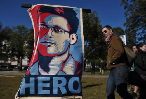 "A picture taken on October 26, 2013 shows a portrait of Edward Snowden declaring him a ""hero"" during a protest against"