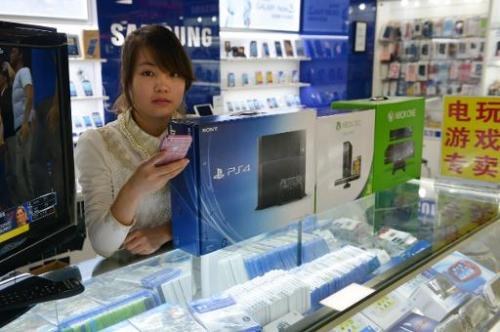 A vendor sells game consoles including Xbox One and Sony's PS4 in a major electronics market in Shanghai on January 8, 2014