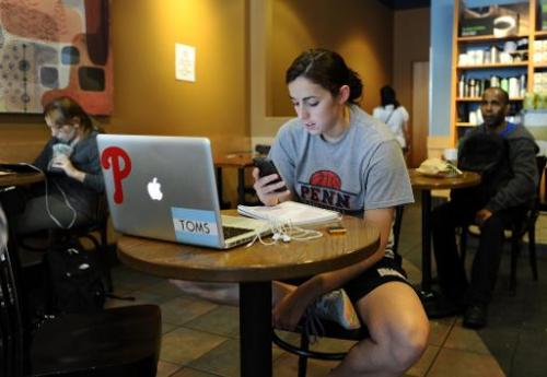 A woman uses her smartphone in a starbucks in Silver Spring, Maryland, on May 9, 2012