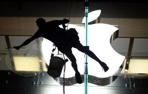 A worker cleans glass panels of the Apple store in the central business district in Sydney, April 8, 2013