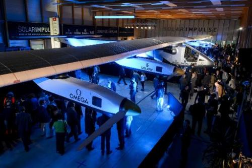 People look at the second Solar Impulse experimental solar-powered plane, the HB-SIB, to be used for a round-the-world voyage ne