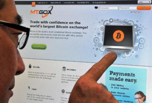This photo illustration shows a man looking at the bitcoin exchange website of MtGox in Tokyo on February 25, 2014