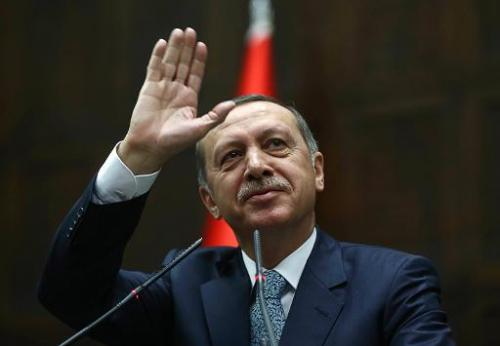 Turkey's Prime Minister Recep Tayyip Erdogan waves to members of his ruling AK Party (AKP) during a session at the Turkish parli