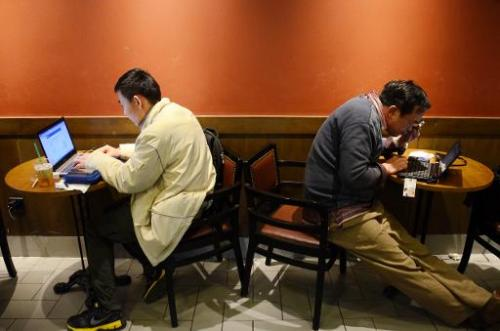 Two Chinese men use their laptop computers at a cafe in Beijing on November 2, 2012
