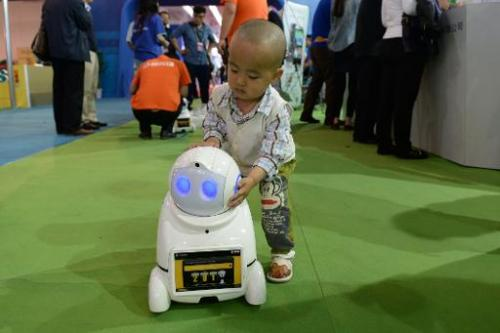 This picture taken on May 14, 2014 shows a child looking at a domestic robot during the 17th China Beijing International High-Te