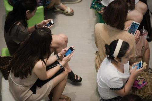 This picture taken on March 21, 2013 shows a group of people sitting down using their smartphones at a shopping mall in Bangkok