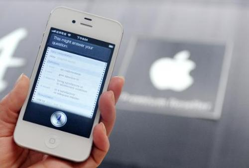 "A woman displays ""Siri"", voice-activated assistant technology, on an Apple iPhone 4S in Taipei on July  30, 2012"
