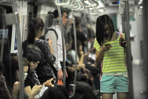 People use their smartphones while travelling on a Mass Rapid Transit train in Singapore, on April 30, 2014