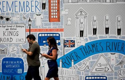 This file photo shows pedestrians walking past an advertising board in central London, on August 22, 2012