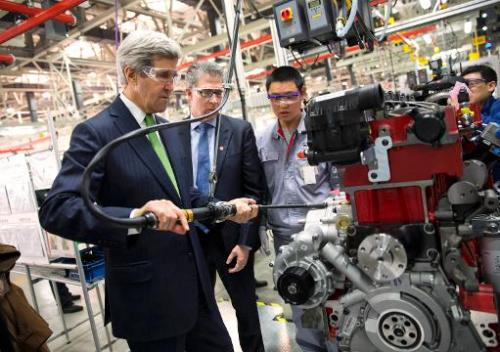 US Secretary of State John Kerry (L) torques an engine bolt during a tour of the Cummins-Foton plant in Beijing on February 15,