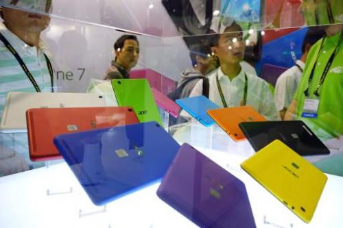 Visitors look at the Acer Iconia One 7 tablet at the Computex tech show in Taipei on June 3, 2014
