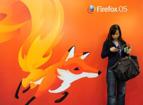 A woman looks at her mobile phone as she stands in front of a poster of Mozilla Firefox onFebruary 27, 2013 at the Mobile World