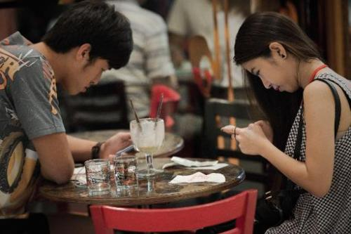 File photo shows a couple reading texts on their smartphones while having drinks together at a shopping mall in Bangkok
