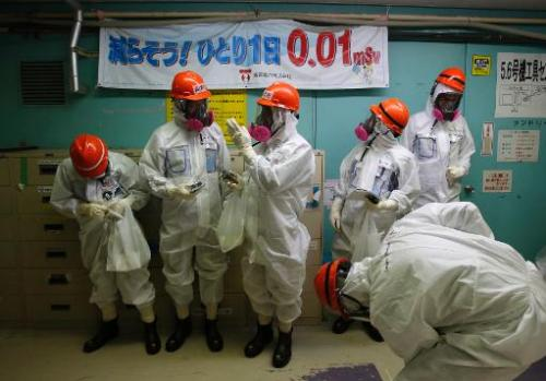 Members of the media and Tokyo Electric Power Co employees inside the number five reactor building at the crippled  Fukushima Da