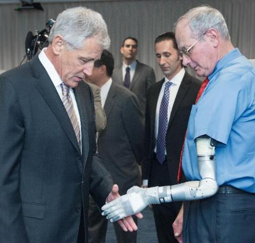 US Secretary of Defense Chuck Hagel greets Fred Downs, who lost an arm in a landmine explosion while fighting in Vietnam and now