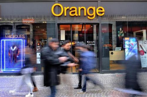 A picture taken on February 24, 2014 in the French northern city of Lille, shows people walking in front of an Orange store