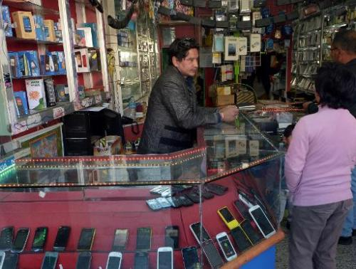 A Bhutanese cellular telephone vendor speaks with potential customers at a shop in Thimphu February 20, 2014
