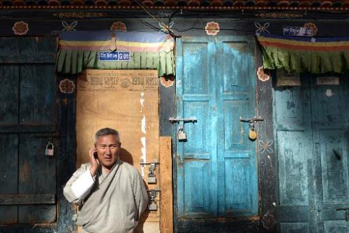 A Bhutanese man speaks on his mobile phone as he stands on a street in Thimphu, February 20, 2014