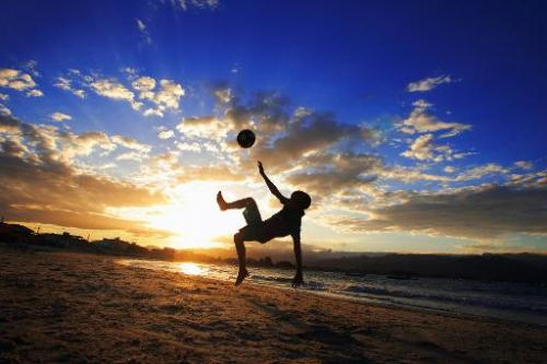 A boy plays football at da Pinheira beach in Santa Catarina, Brazil on April 2006
