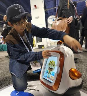 A boy plays with a robot presented  by Future Robots  during the 2014 International CES at the Las Vegas Convention Center on Ja