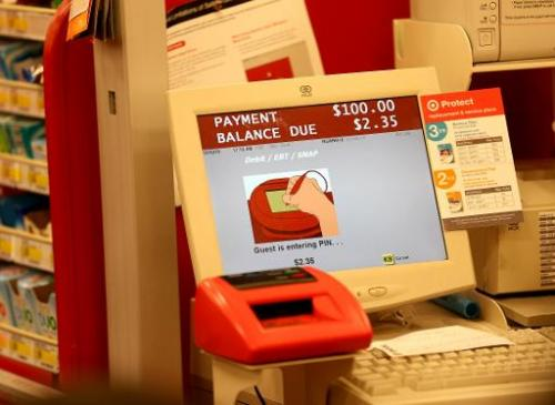 A cash register screen indicates a customer is entering their PIN number at a Target store on December 19, 2013 in Miami, Florid