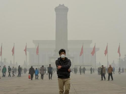 A Chinese tourist wears a face mask in Tiananmen Square as heavy air pollution continues to shroud Beijing on February 26, 2014