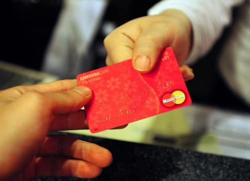 A customer pays his restaurant bill with a credit card in Seoul on April 11, 2011