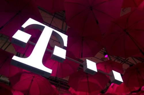 A Deutsche Telekom T-Mobile logo hangs under pink umbrellas at the stand of the German telecommunications giant at the 2014 CeBI