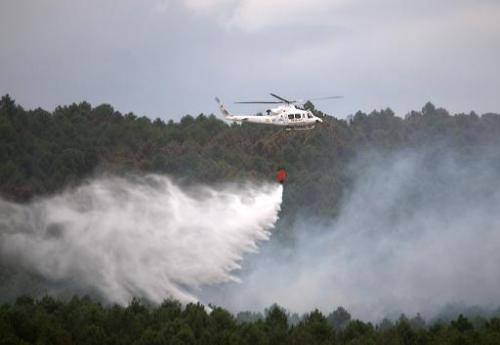 A firefighting helicopter drops water to extinguish a wildfire in Guadalajara, near Veguilla city, on July 19, 2014