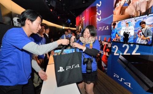 A Japanese customer (R) receives a Sony PlayStation 4 video game console following a countdown ceremony at the Sony building in