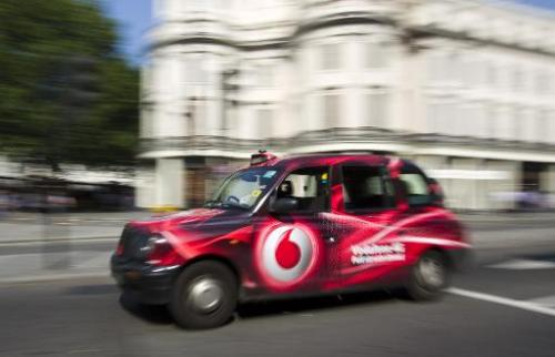 A London black taxi branded with a Vodafone 4G advertisement drives through central London on September 4, 2013