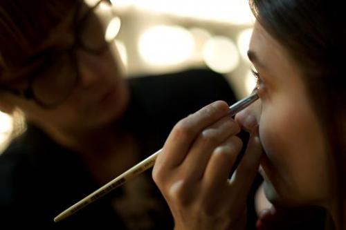 A makeup artist puts finishing touches to a model in Rio de Janeiro on April 16, 2013