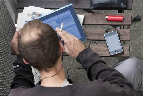 A man is seen working on an iPad, on a balcony in Berlin, Germany, on June 23, 2011