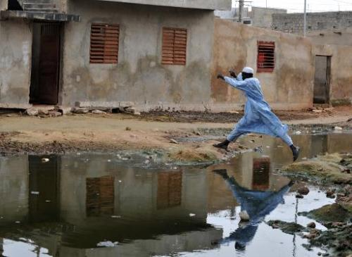 A man jumps over a pond of stagnant water in the suburbs of Dakar on October 9, 2008