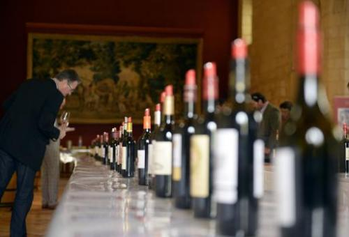 A man looks at bottles of red wine, on April 2, 2014 in Saint-Emilion, southwestern France