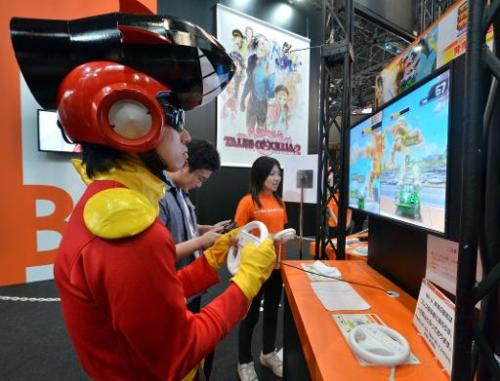 A man plays a videogame on Nintendo's Wii U at a booth of Japanese software house Bandai Namco at the annual Tokyo Game Show in