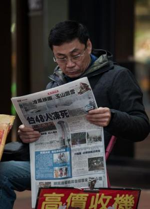 A man reads a Chinese-language newspaper in Hong Kong, on February 12, 2014