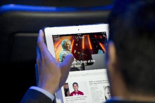A man reads a newspaper article using the Flipboard app on an iPad in Los Angeles, on June 5, 2012