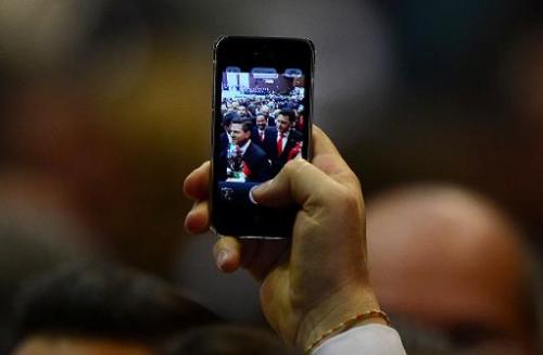 A man shows a picture on his phone of Mexican President Enrique Pena Nieto as he arrives for his inauguration ceremony at the Co