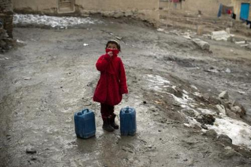An Afghan girl takes a break from carrying water containers up a steep hill in Kabul on February 23, 2014