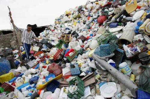An Afghan migrant worker in Qaleh Sheikh village south of Tehran on May 3, 2007 walks over a mound of waste plastic produced by