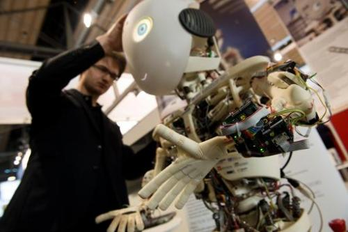 An engineer looks over Roboy, a humanoid robot developed at the Artificial Intelligence Laboratory of the University of Zurich,