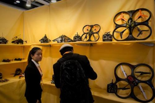 An exhibitor shows drones to a visitor at the 40th Toys and Games Fair in Hong Kong on January 8, 2014