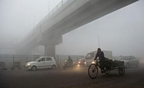 An Indian rickshaw passes under a bridge in New Delhi on January 31, 2013 as pollution hits hazardous levels around the city
